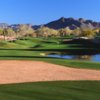 A view of a green with water coming into play and mountains in background at Tatum Ranch Golf Club.