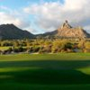A sunny day view of a green at Desert Highlands Golf Club.